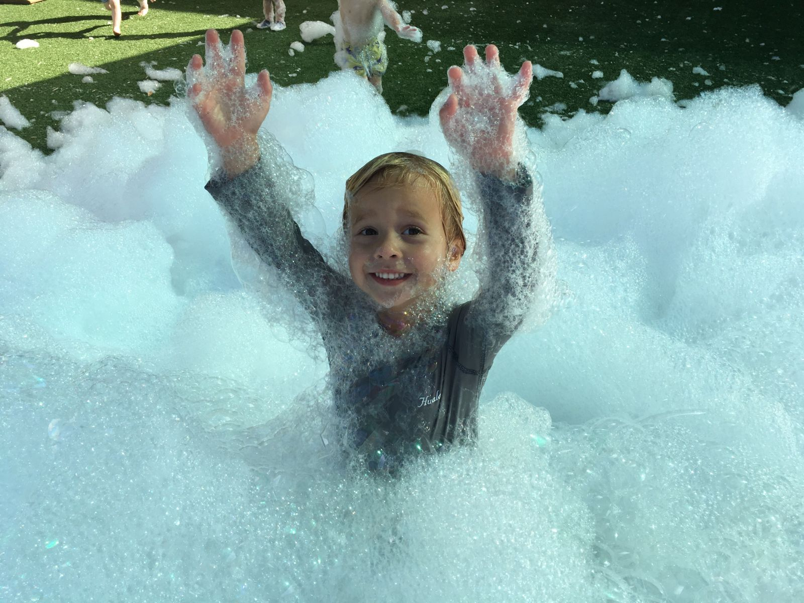 kid playing in foam bubbles