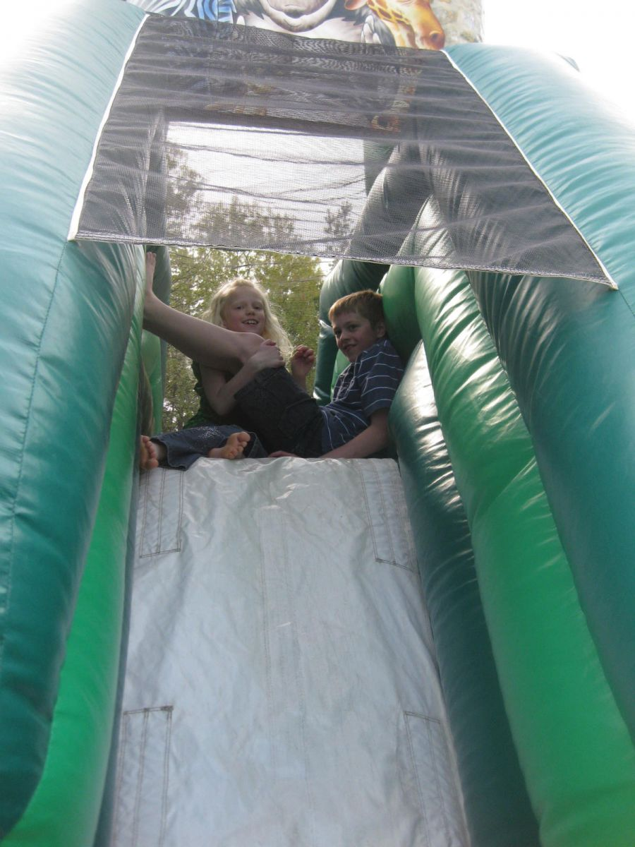 Two Pre-Teens Sitting at the top of the slide inside the Zoo Combo