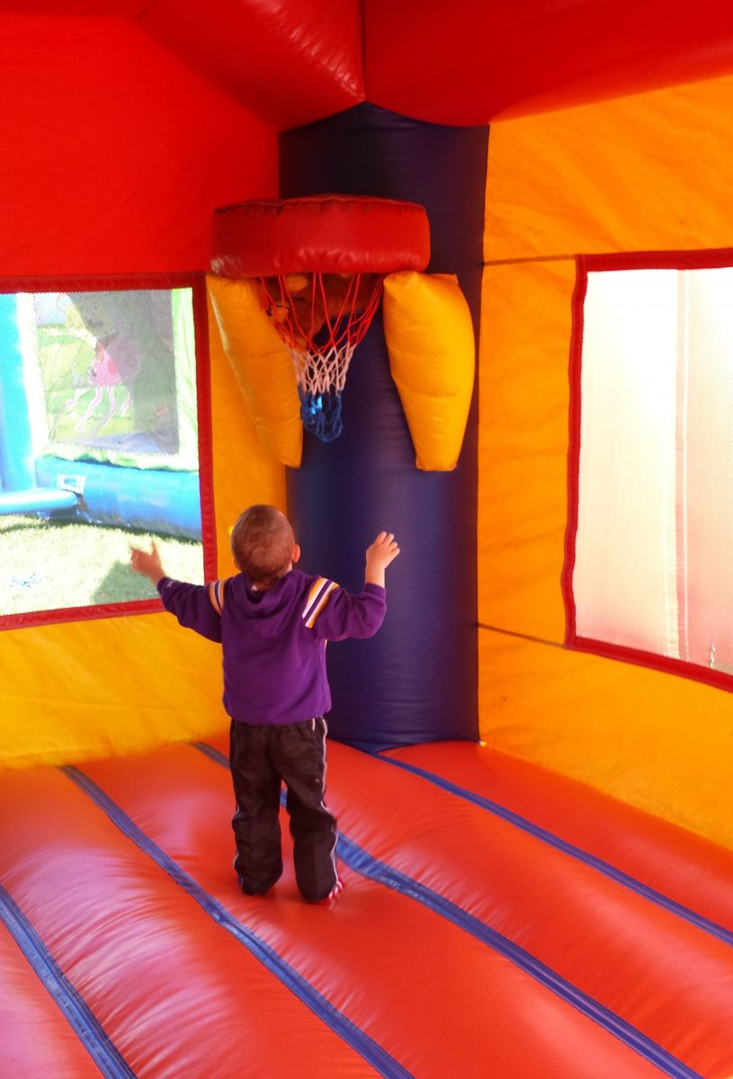 Boy playing basketball inside Castle Combo Inflatable.