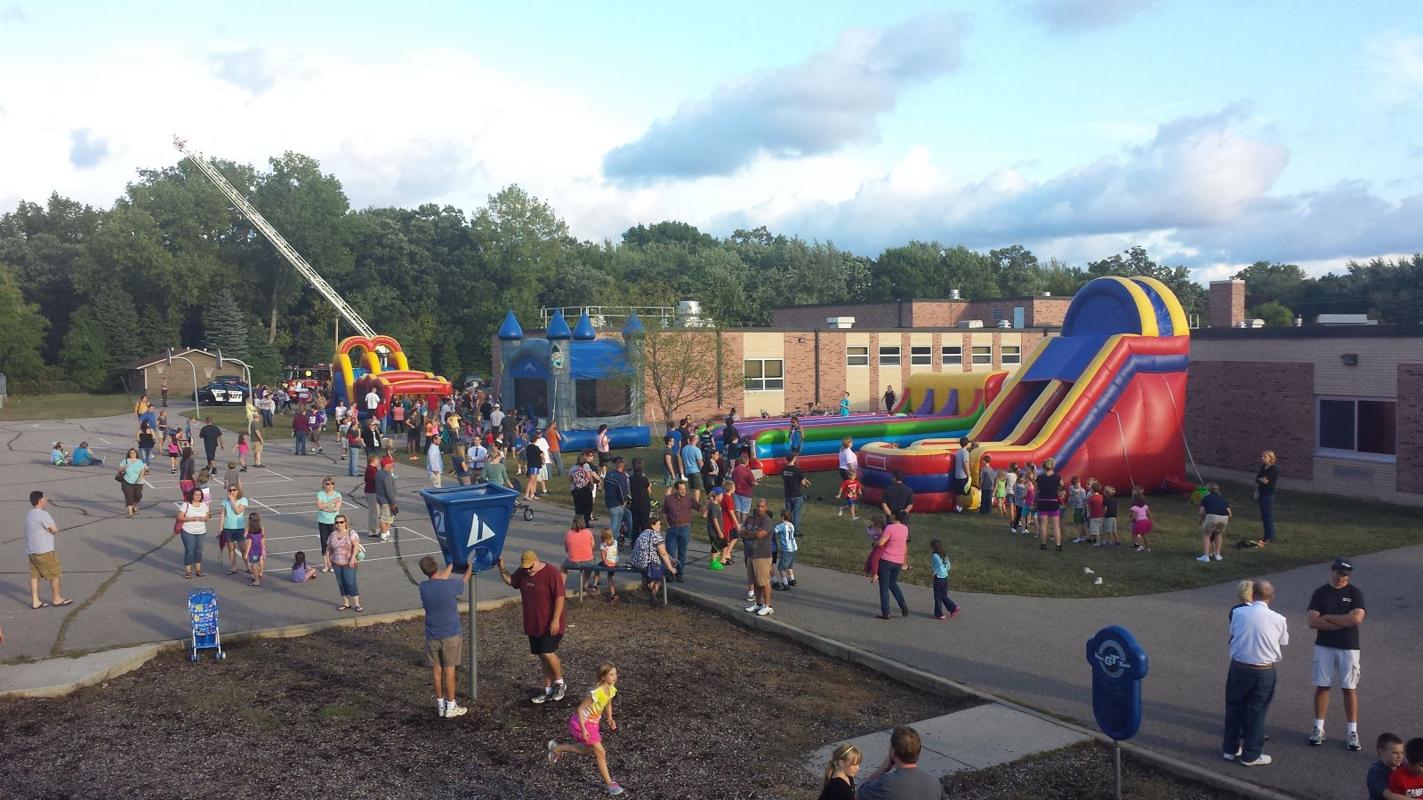 School carnival with giant slide, bounce house, obstacle course, and other inflatables