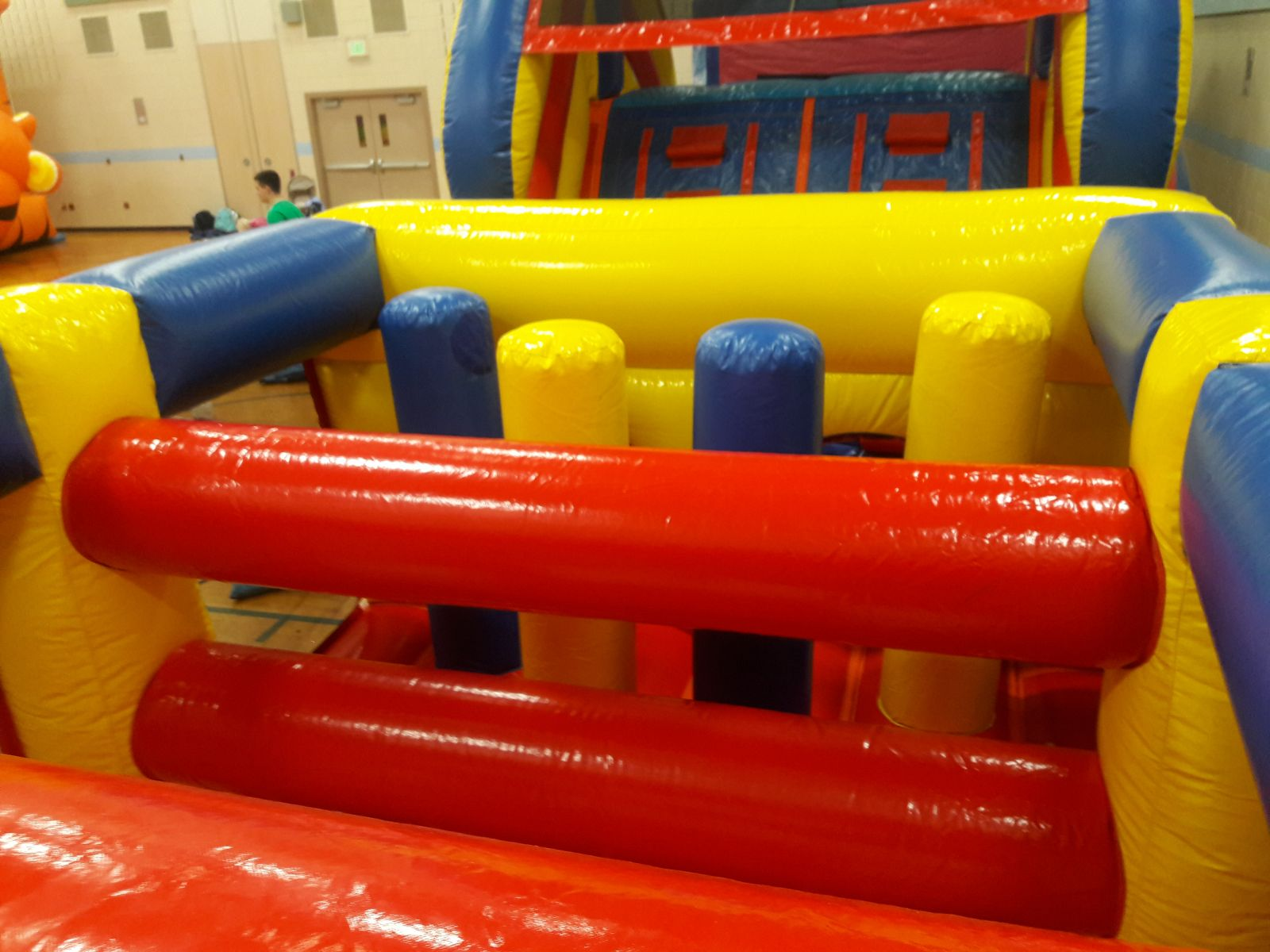 Inflatable logs and pop-up obstacles inside inflatable rental by Froggy Hops