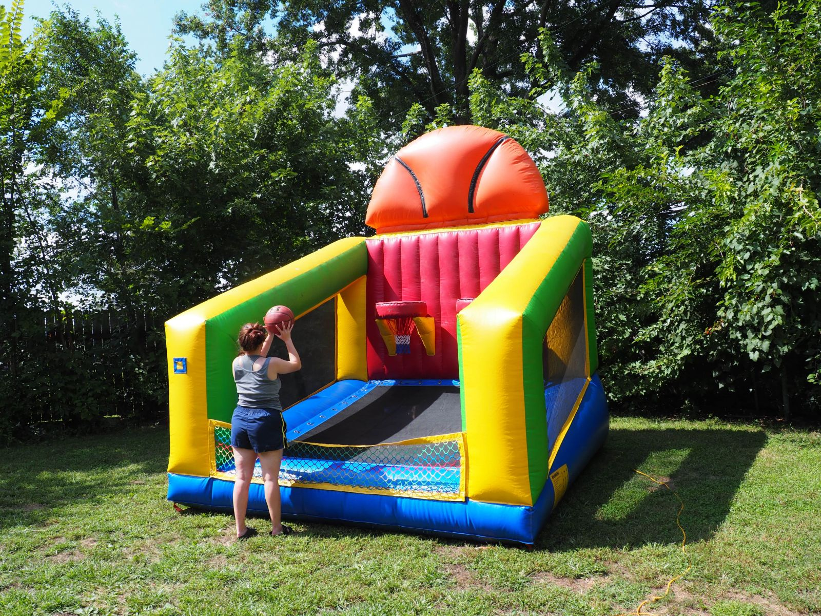 Young girl playing on inflatable basketball hoop game.