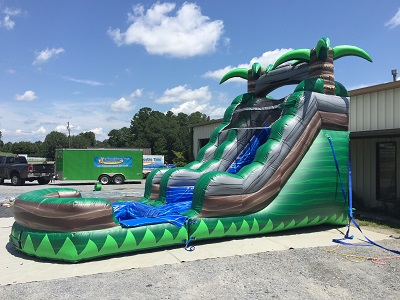 Angled image of the water slide exterior. Two palm trees located on top of the water slide with a pool attached at the bottom of the slide.