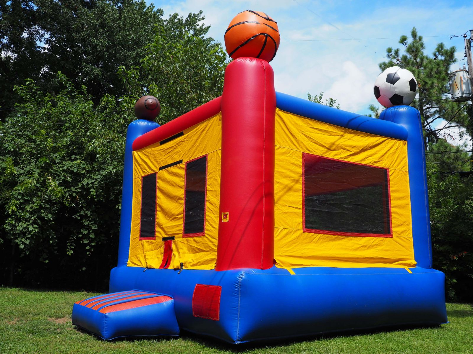 Sports bounce house rental outside on sunny day.