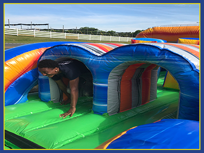 Middle section of a inflatable obstacle course with a person running through a tunnel.