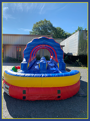 Front view of the slip and slide unique ruffle rings and a two lane slide with pool.