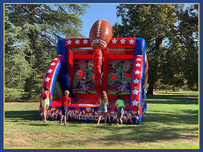 Front view of a football themed interactive inflatable with kids throwing footballs.