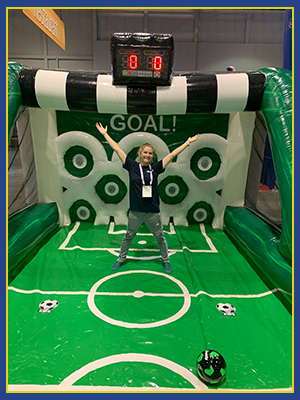 the green, black, and white soccer goal with a woman in the middle of it.