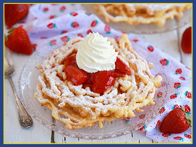 Plated funnel cake with powder sugar, strawberries, and whipped cream.