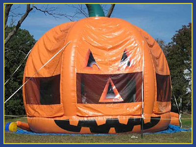 Three Dimensional Pumpkin Themed Bounce House tethered to the ground.