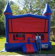 A Blue and Red Castle Bounce House With Basketball Goal