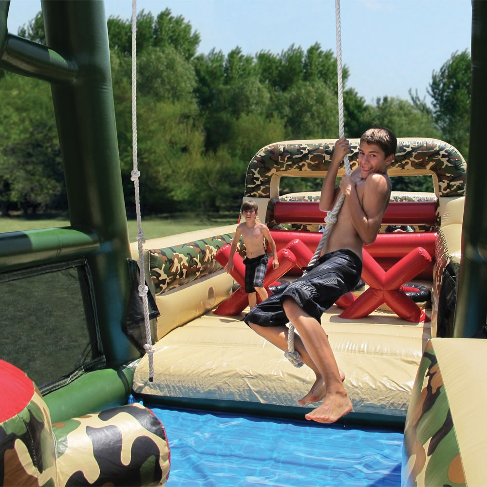 A Boy Swinging through the air on the Boot Camp Obstacle Course