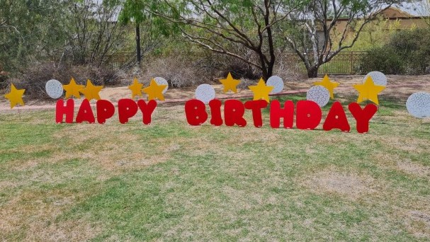 big yellow Happy Birthday yard letters with smileys and