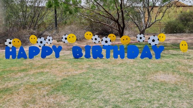 big blue Happy Birthday yard letters with smileys and soccer balls