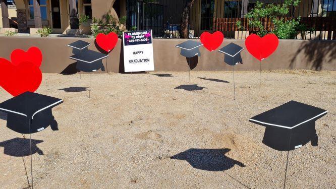 Graduation caps and hearts yard sign