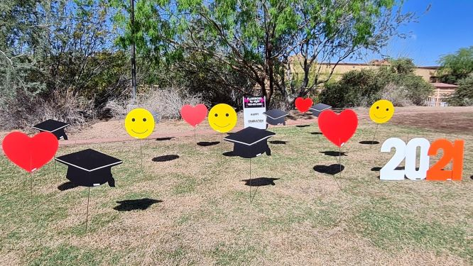 yard display of graduation caps, hearts, 2021 and smiley faces