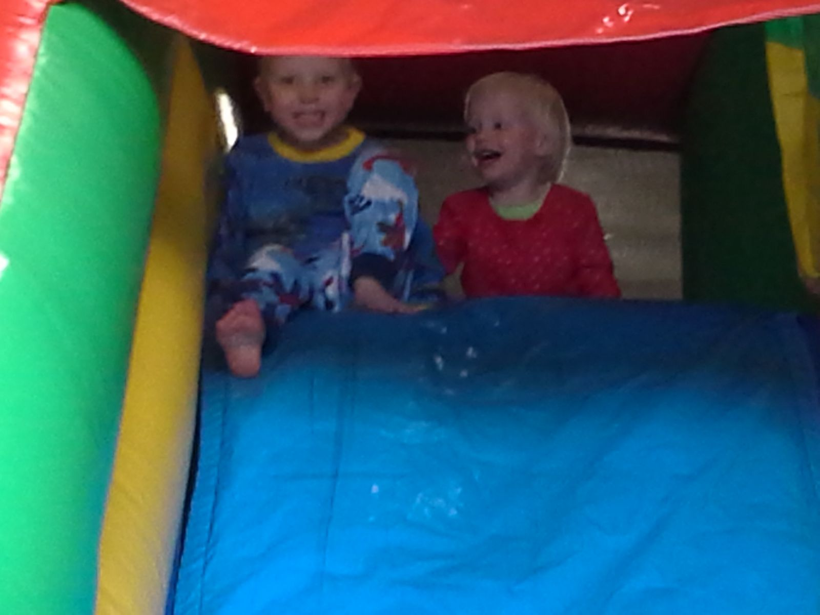 2 Kids at the top of the slide in a Castle Combo Inflatable