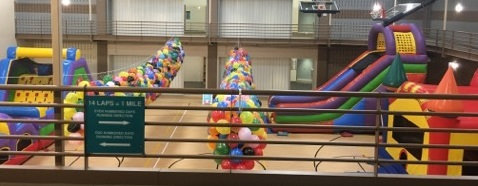 Obstacle course, giant slide, and bounce house inside community center gym