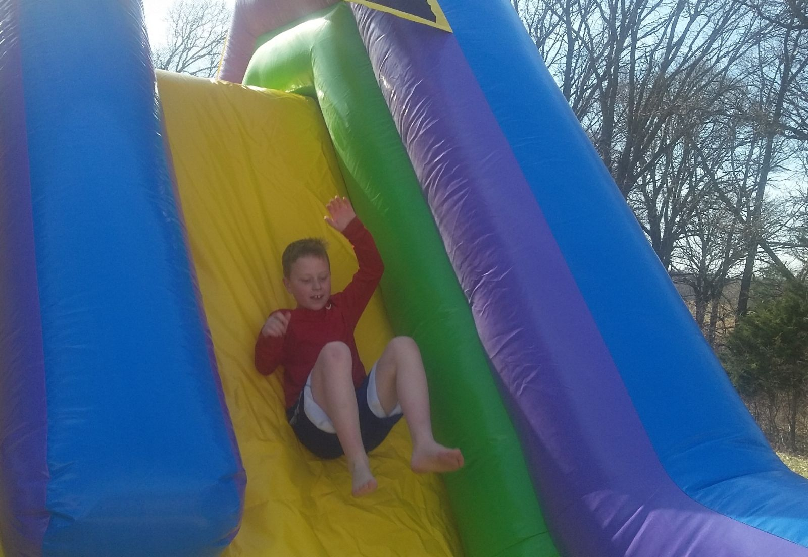 Boy going down slide on conquer obstacle course