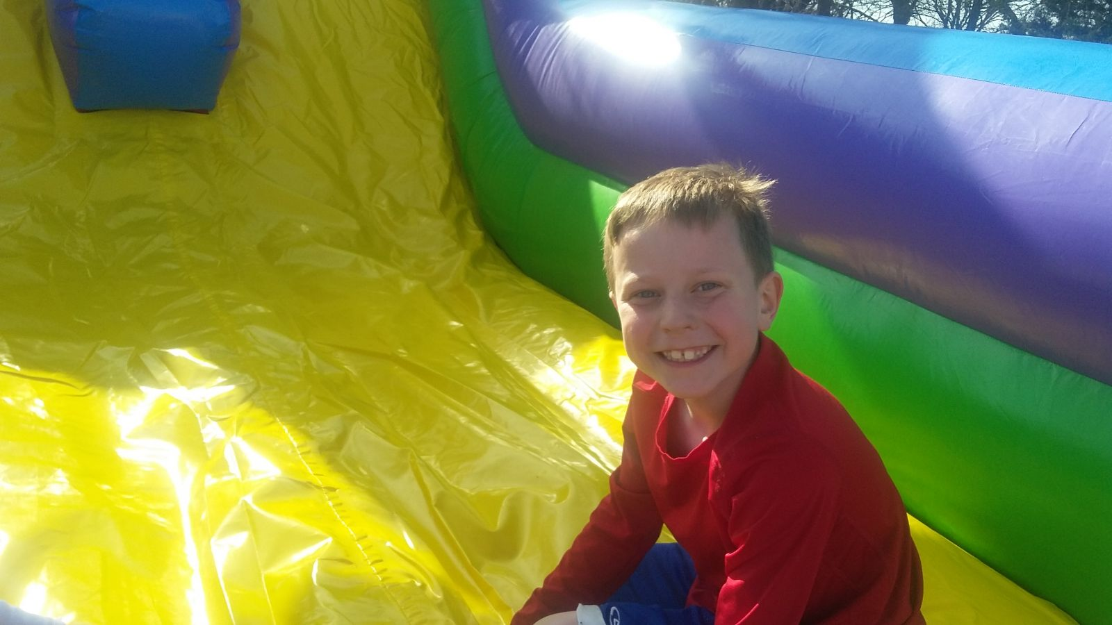 Boy on slide on conquer inflatable obstacle course rental from Froggy Hops