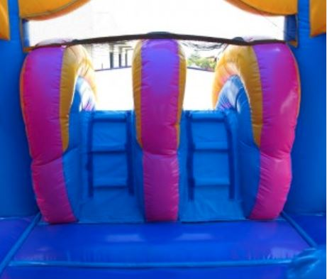 Climbing wall up to slide on pink bounce house rental