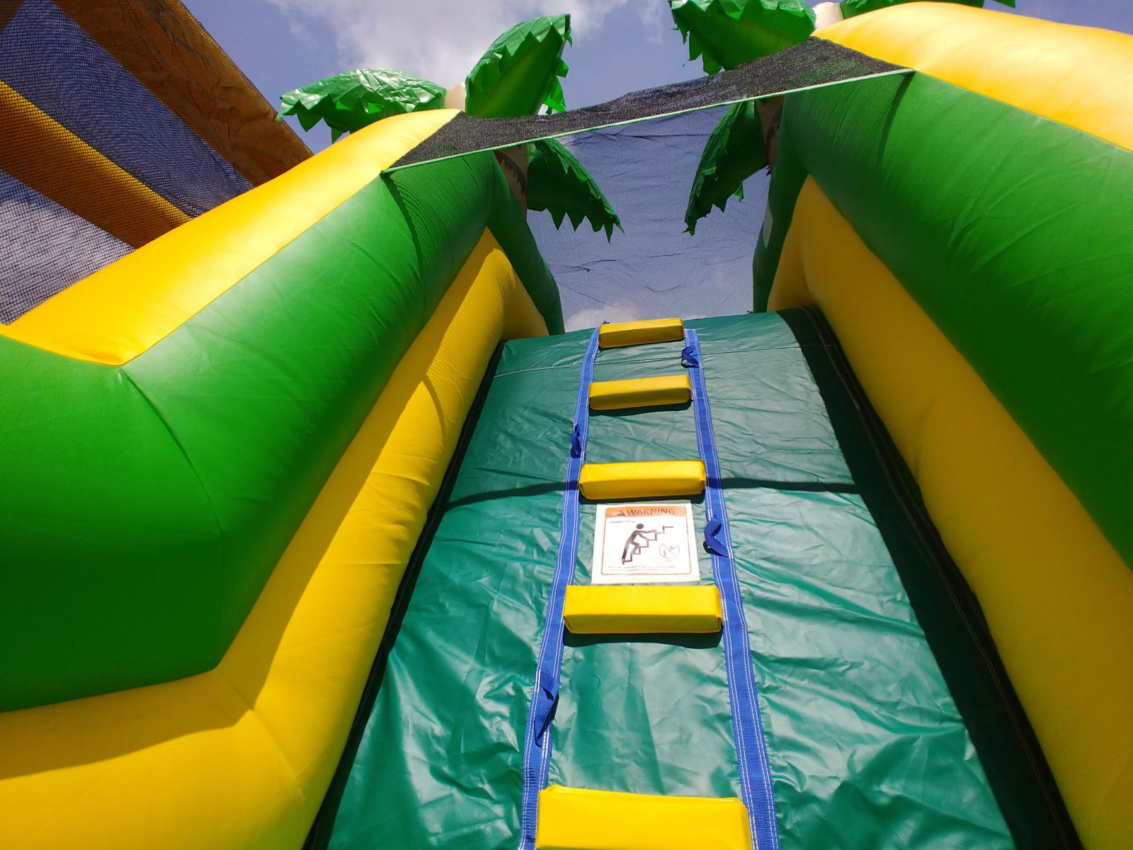 Climbing wall inside tropical inflatable obstacle course