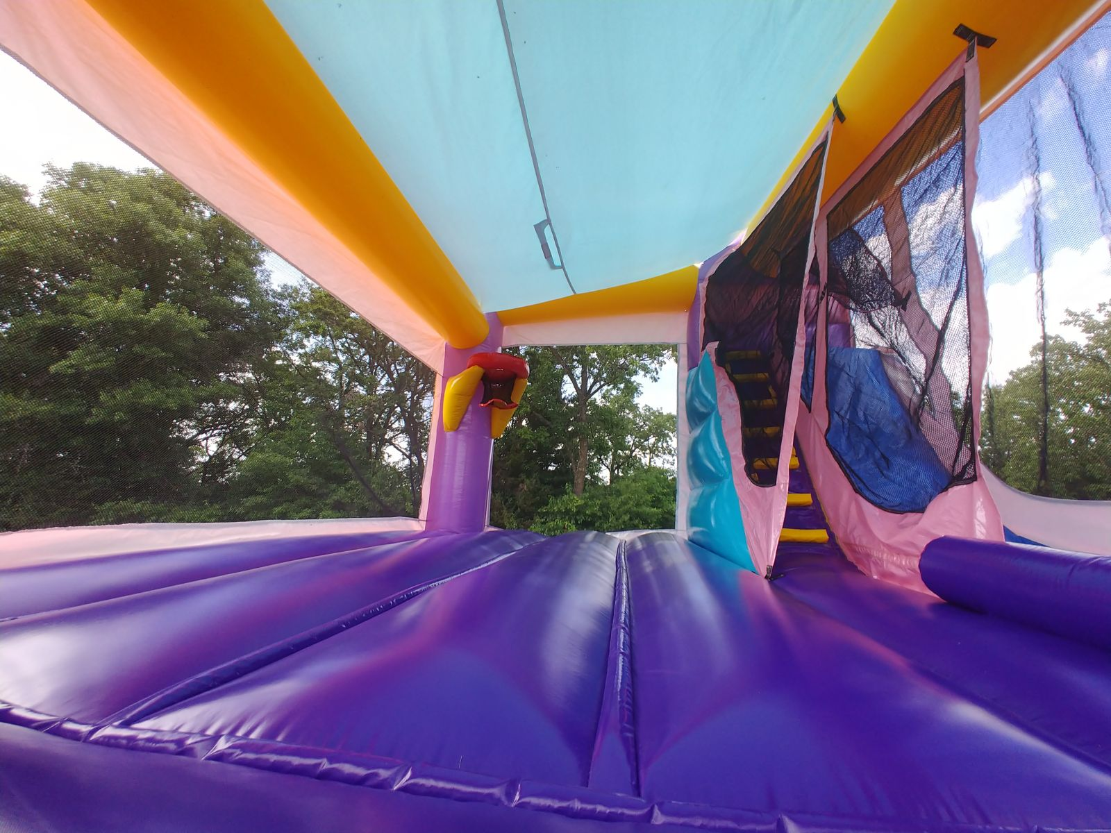 Entrance view of inflatable combo jumping area with basketball hoop and slide