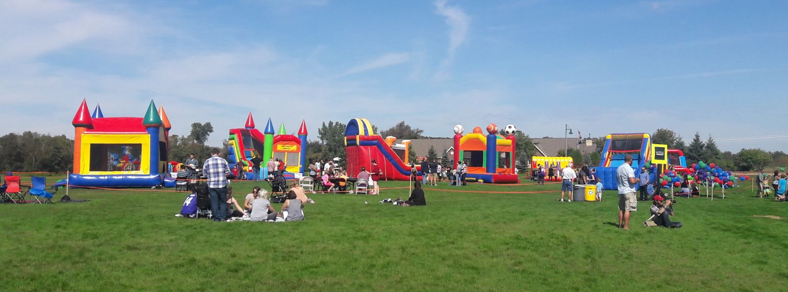 Giant inflatable slide, bounce house, combo, and other inflatables at a church field event.