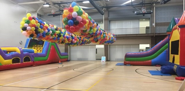 Inflatables inside gym including large obstacle course, slide, and bouncy castle
