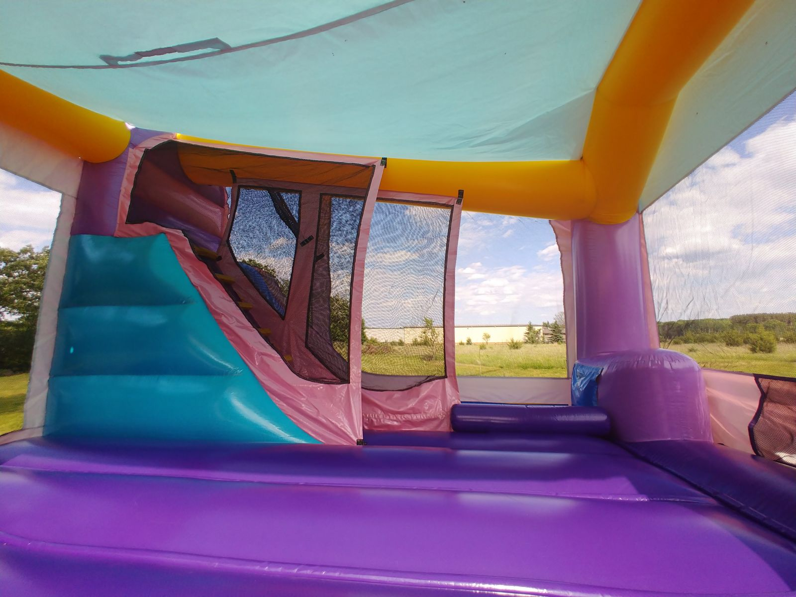 Interior view of slide and climbing wall area inside bounce house rental from Froggy Hops