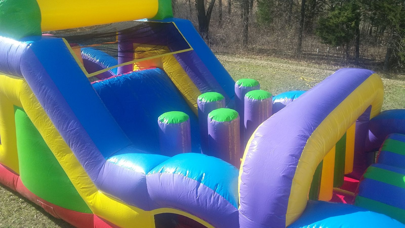 Obstacle course slide into pop-ups and inflatable hanging bars
