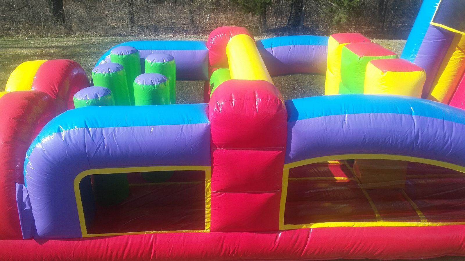 Sideview of inflatable obstacles within the 68' Conquer Obstacle Course Bounce House