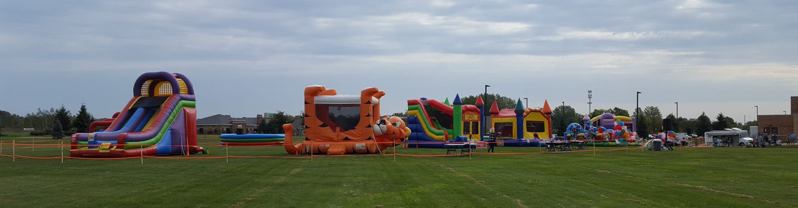 Tiger Belly Bouncer, GIANT Slide, Combo, and other inflatables at a church event.