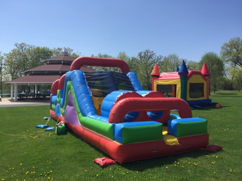Obstacle course and bounce house setup outdoors at a city park
