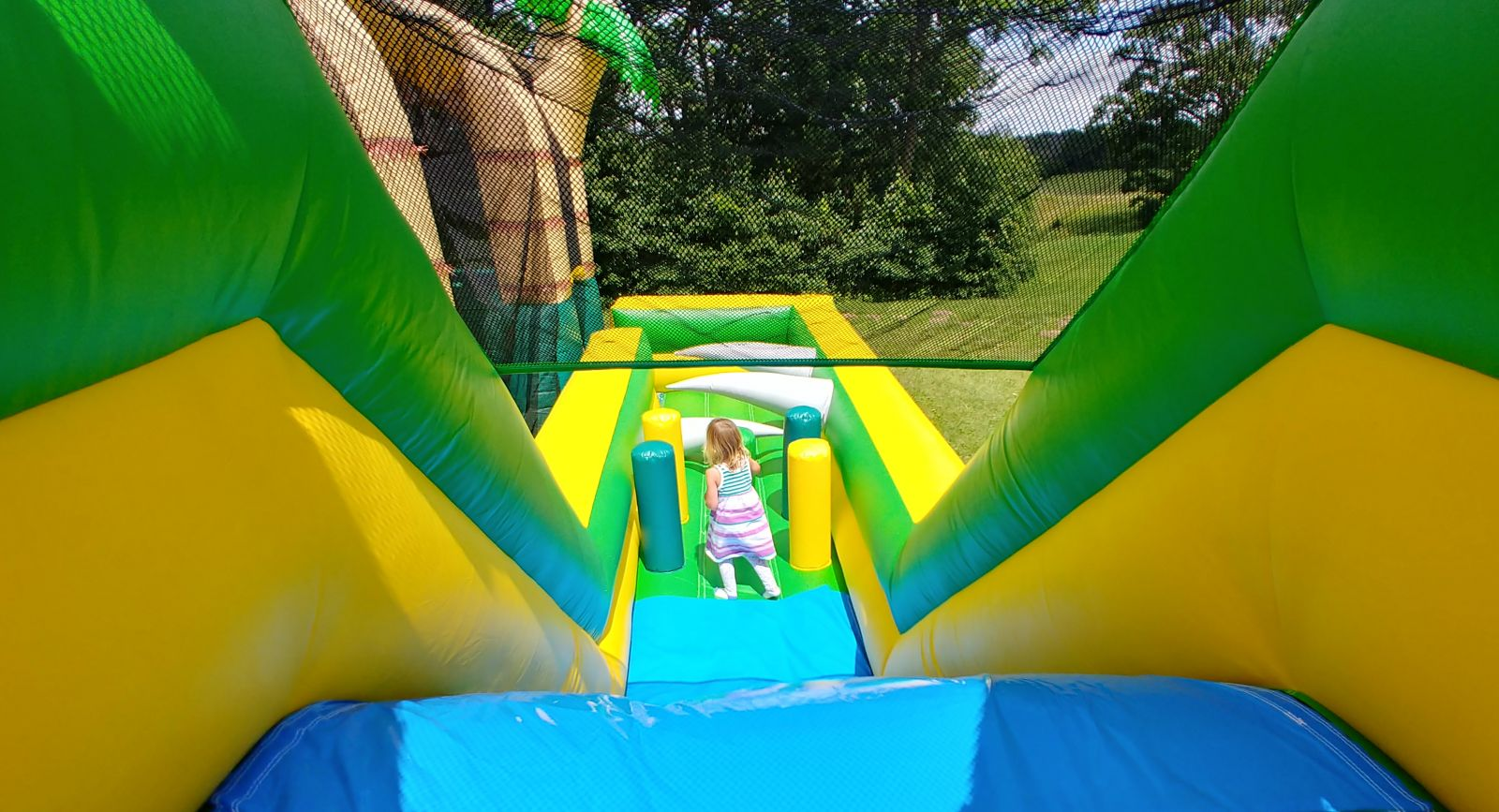 Young girl on tropical inflatable obstacle course
