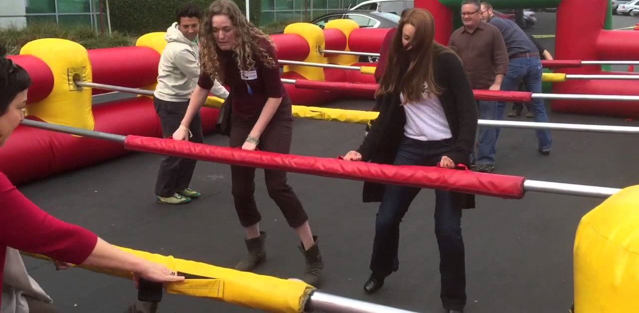 Adults playing inflatable human foosball outdoor