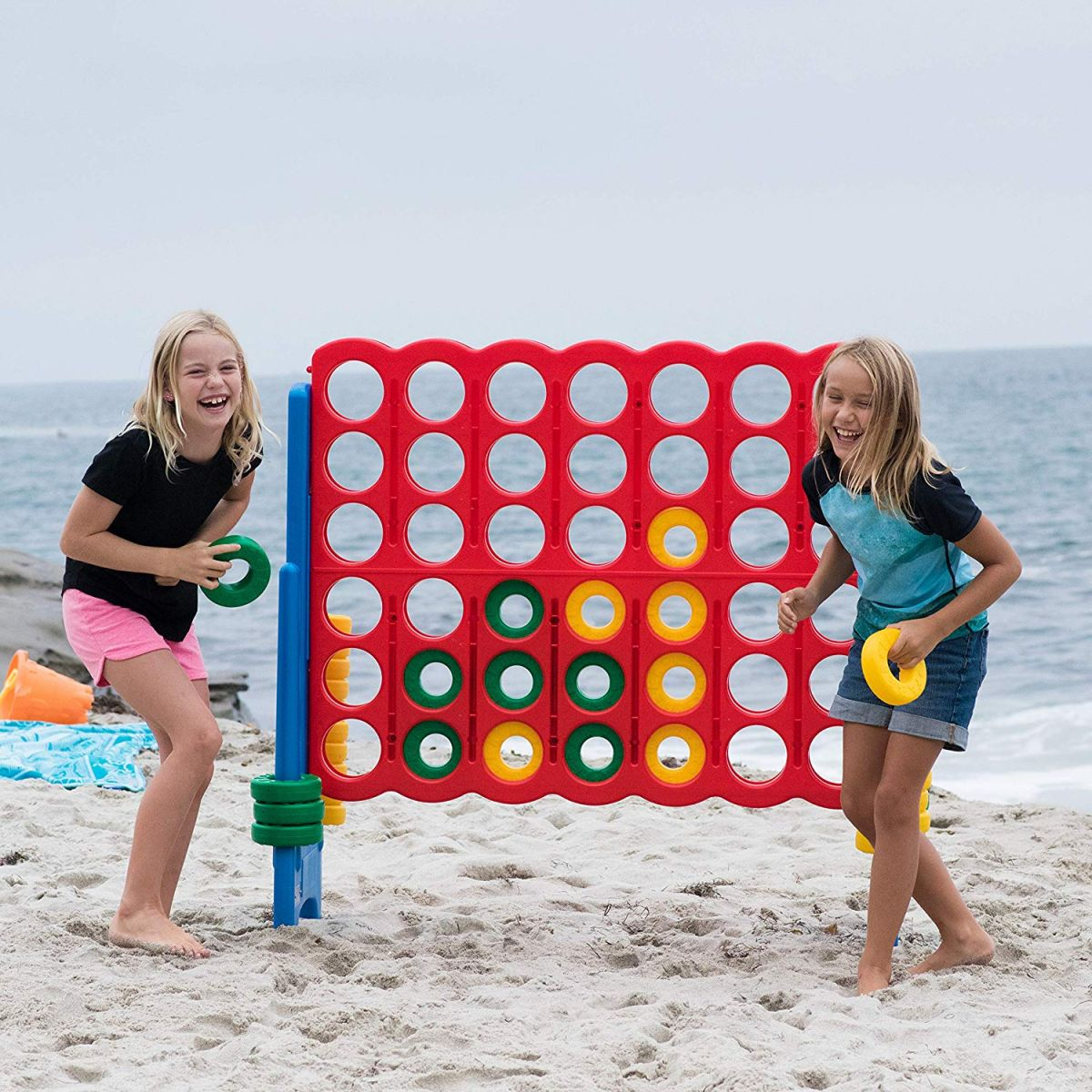 Girls playing giant connect 4 game at the beach