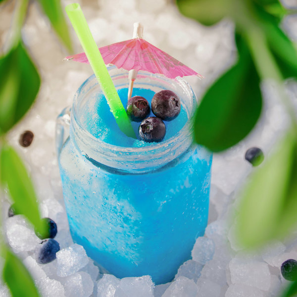 Blue Frozen Drink with green straw and pink umbrella