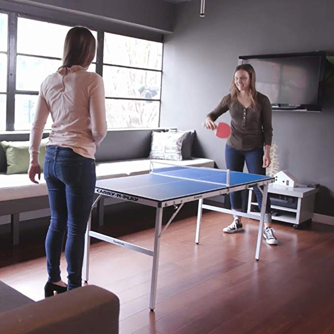 Two girls playing on a mini ping pong table