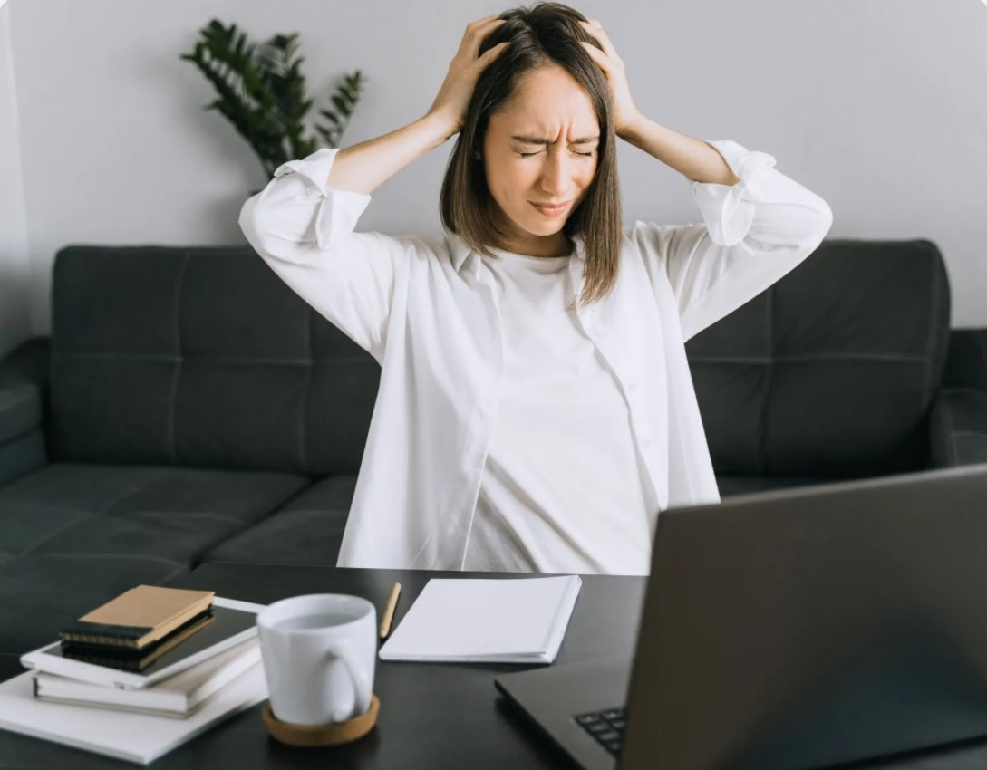 portrait-of-tired-young-woman-with-laptop