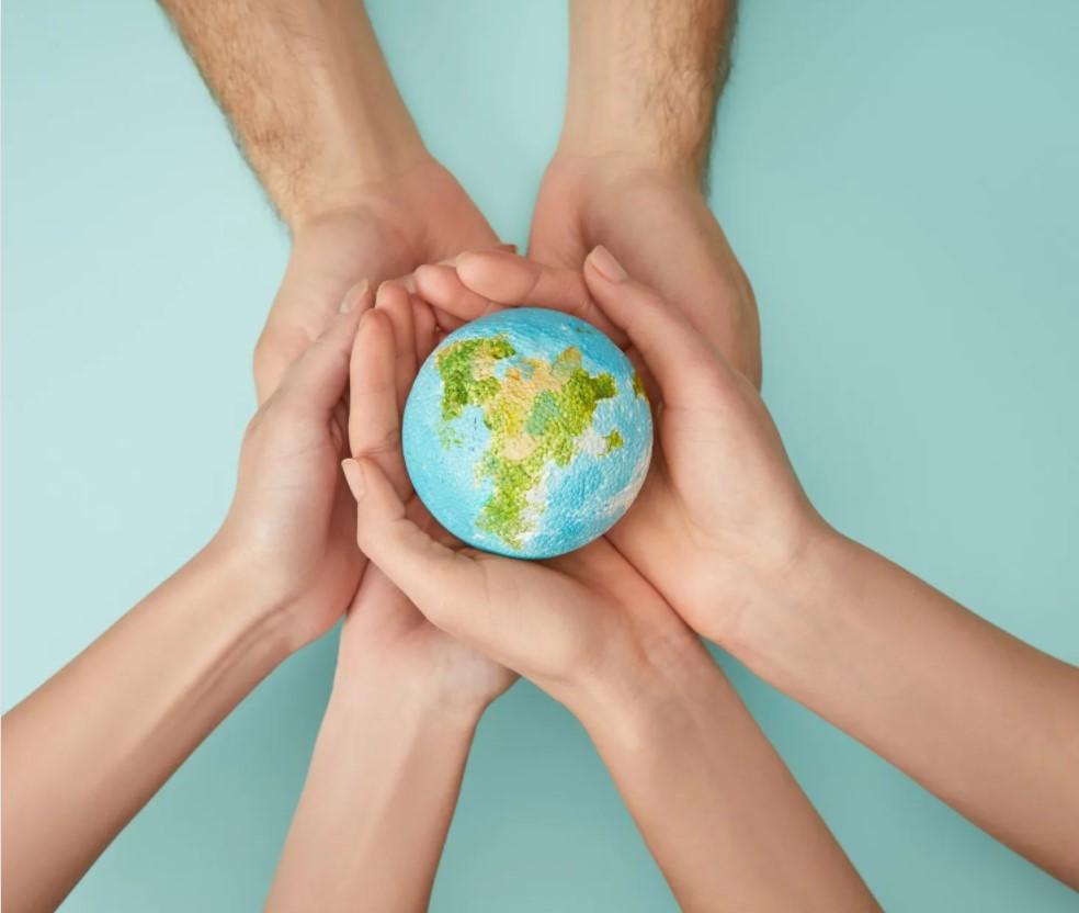 photo of hands holding globe