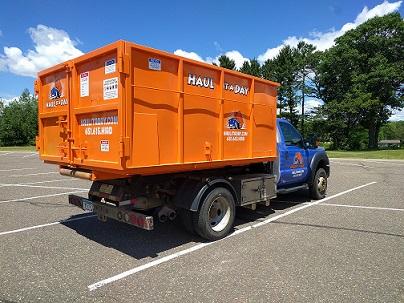 Photo of orange 15 yard roll-off dumpster on blur Haul it a Day truck in parking lot