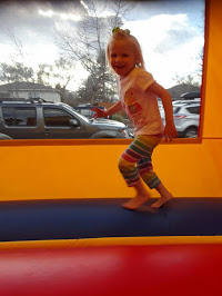 Little girl smiling while she plays in the bouncy house.
