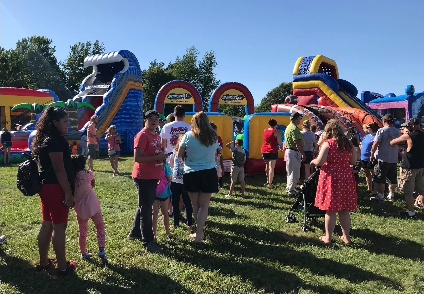 Kids and adults near inflatable slides & bounce houses