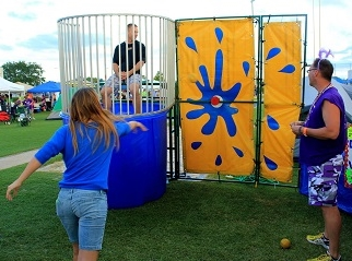 Adult throwing a ball at the dunk tank